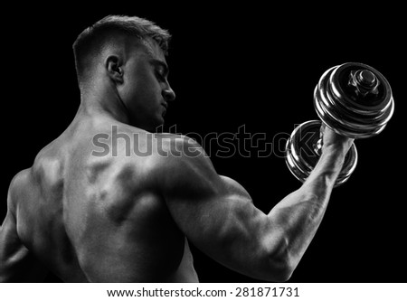 Closeup of a handsome power athletic man bodybuilder doing exercises with dumbbell. Fitness muscular body on dark background. Black and white photo