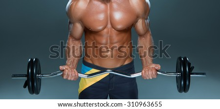 Closeup of a handsome power athletic man bodybuilder doing exercises with  with barbell. Fitness muscular body on dark background. - stock photo