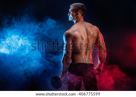Closeup of a handsome power athletic man bodybuilder resting while stand with dumbbell. Fitness muscular body on dark  smoke background. Perfect male. Awesome bodybuilder, tattoo, posing.  - stock photo