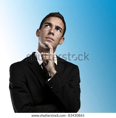 Closeup of a handsome young business man thinking against blue background - stock photo