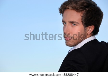 Closeup of a handsome young man in a suit - stock photo