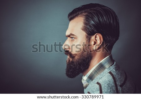 Closeup of a handsome young man with retro look, side view. Studio shot - stock photo