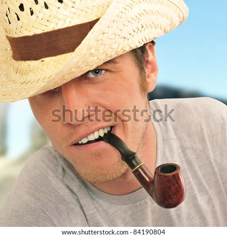 Closeup of a happy brutal young man looking at camera and smoking his pipe. American farmer - stock photo