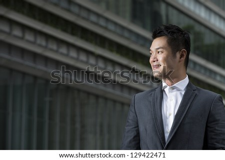 Closeup of a happy young Chinese business man looking away. Asian man smiling & looking away with blurred office buildings as a background. - stock photo