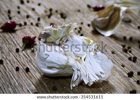 closeup of a head of garlic and some garlic cloves on a rustic wooden table - stock photo