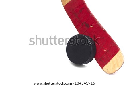 closeup of a hockey stick with a puck isolated on white - stock photo