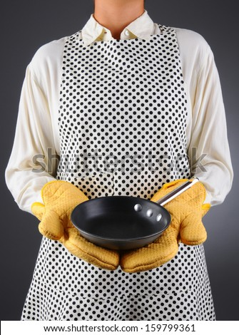 Closeup of a homemaker in an apron and oven mitts holding a pan. Vertical format over a light to dark background. Woman is unrecognizable. The pan is empty - ready for you to add food or copy.
