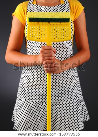 Closeup of a homemaker in an apron holding a sponge mop in front of her torso. Vertical format over a light to dark background. Woman is unrecognizable.
