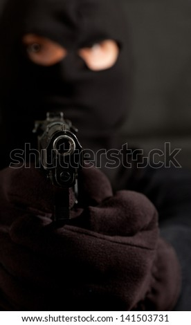Closeup of a hooded robber with a gun - stock photo