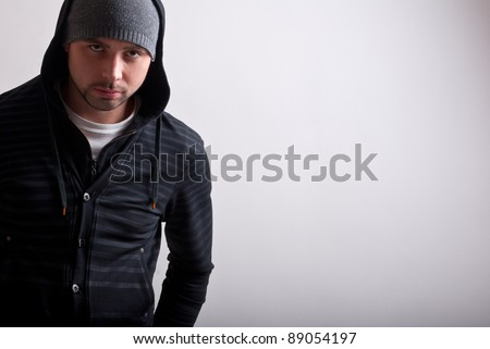 Closeup of a hooded teenager looking menacing - stock photo