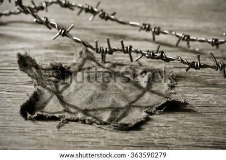 closeup of a Jewish badge and barbed wire on a rustic background, in sepia toning - stock photo