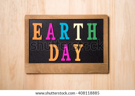 """closeup of a label-shaped chalkboard with the text earth day. colorful letter """"earth day"""" on a blackboard - stock photo"""
