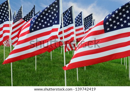 Closeup of a large group of American Flags in a field of grass with a blue cloudy sky. - stock photo