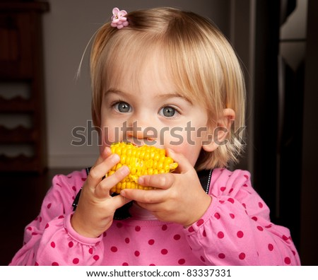 Closeup of a little girl taking a bite out of a corn on the cob - stock photo