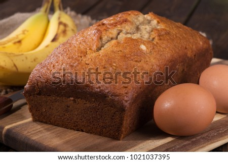 Closeup of a loaf of banana nut bread with the ingredients of brown egg and bananas on the side