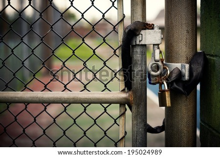 Closeup of a locked padlock securing a metal chain-link gate. - stock photo