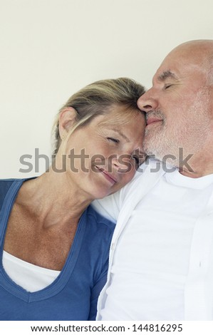 Closeup of a loving middle aged couple against wall - stock photo