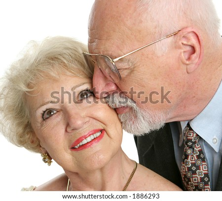 Closeup of a loving senior man gives his beautiful wife a kiss on the cheek. - stock photo