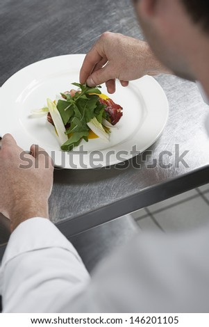Closeup of a male chef preparing salad in kitchen - stock photo