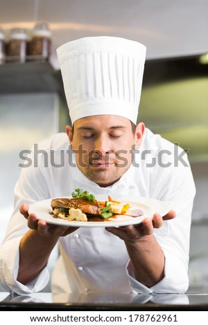 Closeup of a male chef with eyes closed smelling food in the kitchen - stock photo