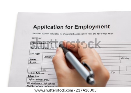 Closeup of a male hand holding a pen completing a job application form in a career and employment concept - stock photo