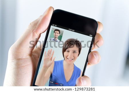 Closeup of a male hand holding a smartphone during a skype video call with his girlfriend or wife - stock photo