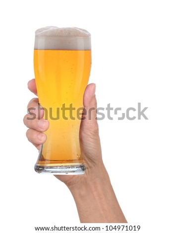 Closeup of a male hand holding up a glass of beer over a white background. Vertical format with condensation side of the beer glass. - stock photo