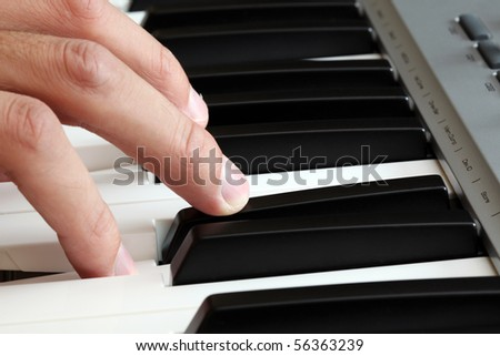 Closeup of a male hand playing a piano - stock photo