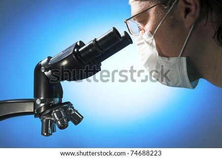 Closeup of a male researcher looking through microscope - stock photo