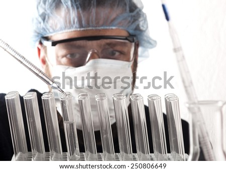 Closeup of a male scientist filling test tubes with pipette in laboratory. - stock photo