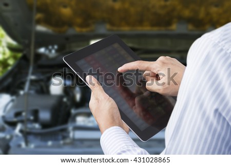 Closeup of a man checking the car on touchscreen tablet in a garage