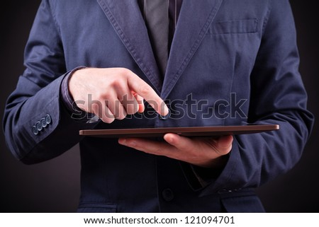Closeup of a man holding a digital tablet on black background