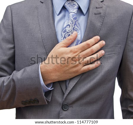 closeup of a man in a suit with his hand over his heart - stock photo