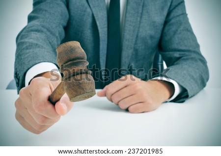 closeup of a man in suit about to struck a gavel - stock photo