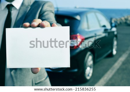 closeup of a man in suit holding a blank signboard with a car in the background - stock photo