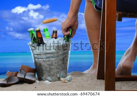 Closeup of a man on vacation sitting in a wooden chair at the beach reaching into a bucket filled with ice and beer bottles. - stock photo