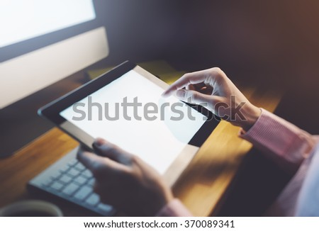 Closeup of a man pointing finger  to a computer monitor with a blank screen blue against a background of bokeh light in the office horizontal - stock photo