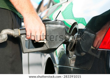 Closeup of a man pumping gas into his automobile.