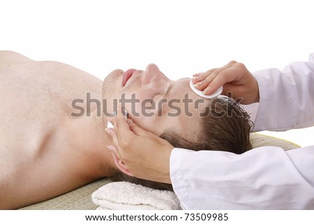 Closeup of a man receiving facial massage from a woman - stock photo