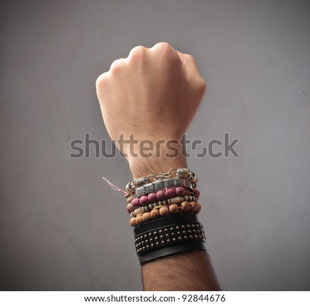 Closeup of a man's arm full of bracelets - stock photo