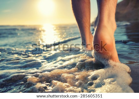 Closeup of a man's bare feet walking at a beach at sunset, with a wave's edge foaming gently beneath them, toned colors - stock photo