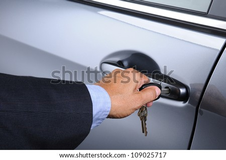 Closeup of a man's hand inserting a key into the door lock of a car. Horizontal format. Car and man are unrecognizable.