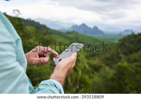 Closeup of a man's hand is holding mobile phone with copy space screen against blurred jungle landscape. Young male is searching information on cell telephone during summer adventure in Thailand - stock photo