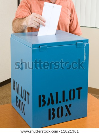 Closeup of a man's hand placing his ballot in the box. - stock photo