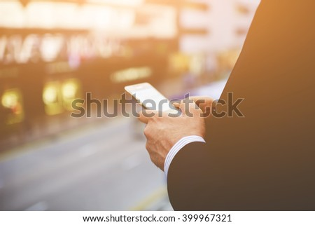 Closeup of a man`s hands is holding cell telephone with blank copy space screen for your advertising text message or information content. Businessman is reading news in internet via mobile phone - stock photo