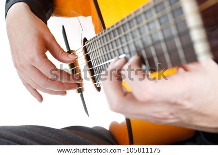 Closeup of a man's hands playing the guitar - isolated on white
