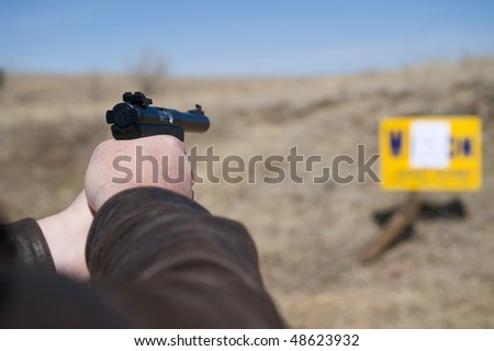 Closeup of a man's hands shooting a pistol on the target range. - stock photo