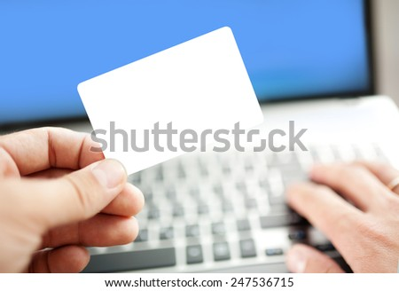 Closeup of a man shopping online using laptop with credit card. Credit card is blank. Credit card template - stock photo