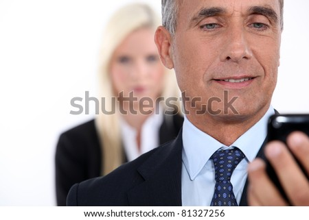 Closeup of a man smiling in front of his cellphone - stock photo