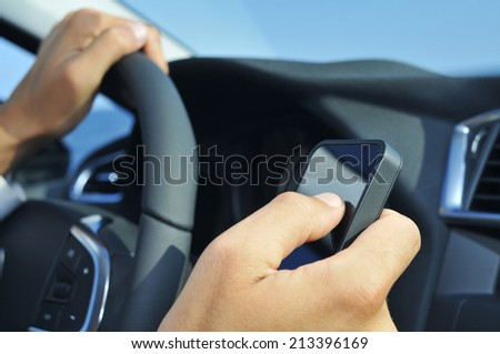 closeup of a man using a smartphone while driving a car - stock photo